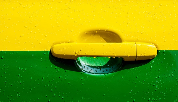 Porta di automobile gialla e verde nella pioggia del giorno - primo piano Foto Premium