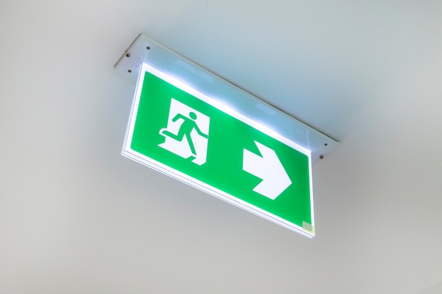 Porta di uscita d'emergenza dal fuoco. porta di uscita dal soffitto. segno verde dell'uscita di sicurezza che mostra il modo. Foto Premium