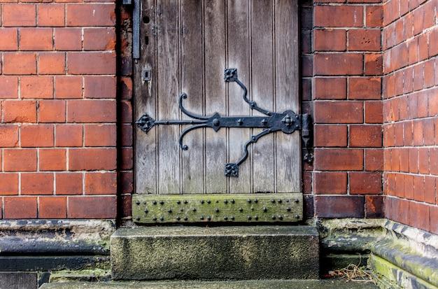 Porta in legno e muro di mattoni in una vecchia cattedrale Foto Premium