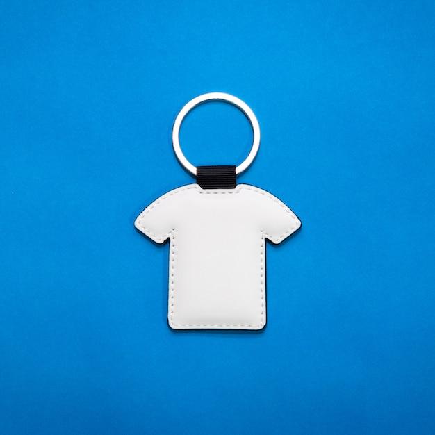 Portachiavi in pelle a forma di camicia su sfondo blu carta Foto Premium