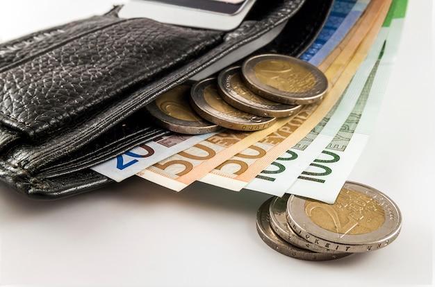 Portafoglio aperto da uomo in pelle con banconote in euro, monete e carta di credito all'interno isolato su sfondo bianco. Foto Premium