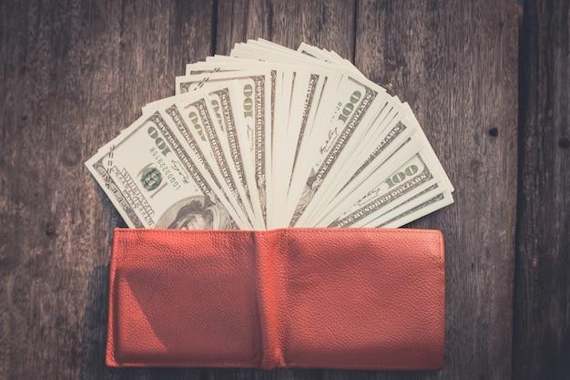 Portafoglio con dollari usa sul tavolo di legno Foto Premium