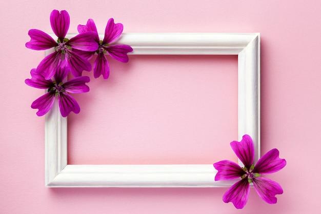 Portafoto in legno bianco con fiori viola su fondo di carta rosa, Foto Premium