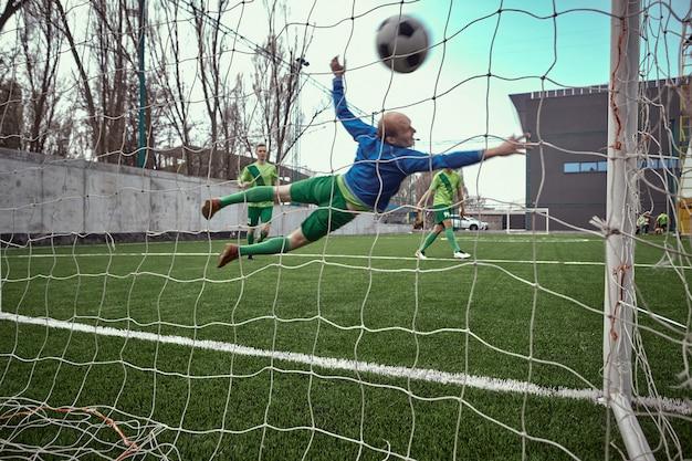 Portiere di calcio calcio facendo immersioni salvare Foto Gratuite
