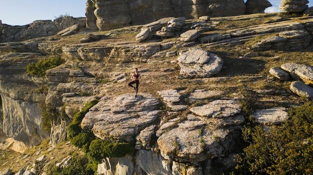 Posa dell'equilibrio della pratica yoga nel cuore della natura Foto Gratuite