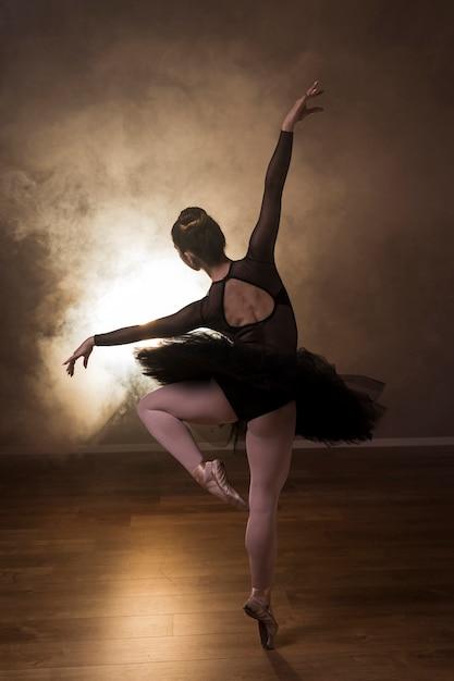 Posa della ballerina di vista posteriore in fumo Foto Gratuite