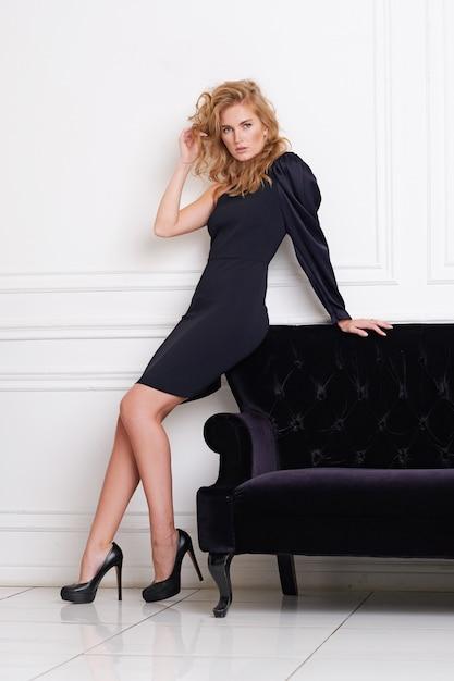 Posa di modello della bella donna in vestito elegante nello studio. Foto Premium