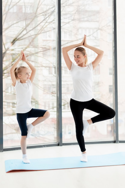 Posa di yoga con la madre e la figlia di smiley a casa Foto Gratuite