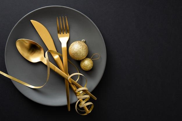 Posate d'oro servite sul piatto per la cena di natale Foto Premium