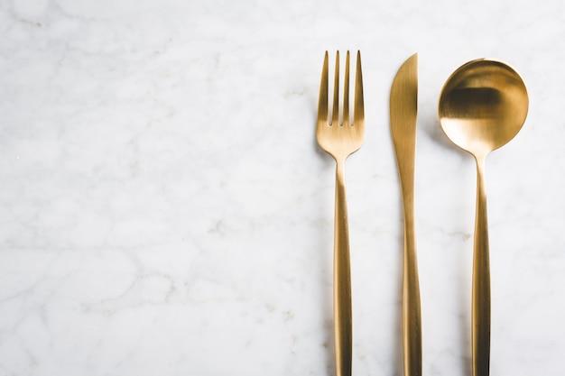 Posate d'oro su marmo Foto Gratuite