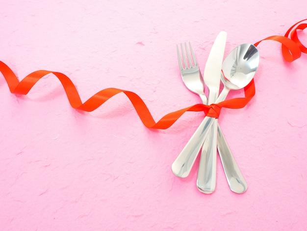 Posate e cuori sul tavolo rosa Foto Premium