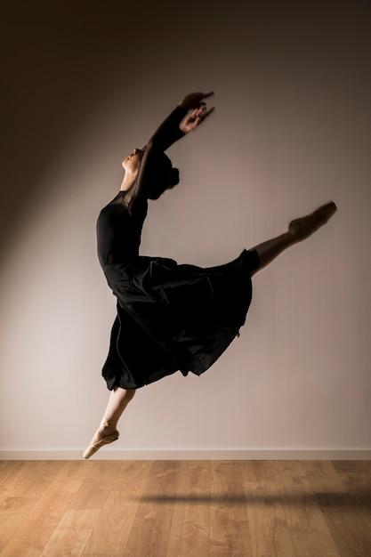 Posizione di salto della ballerina di vista laterale Foto Gratuite