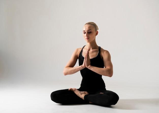 Posizione meditating della donna a tutto campo Foto Gratuite