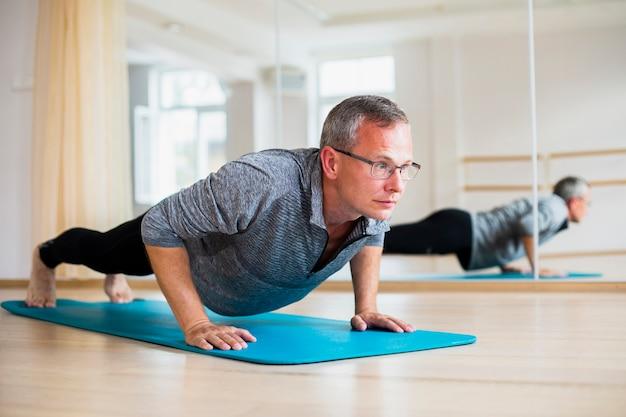 Posizioni di yoga di pratica dell'uomo adulto Foto Gratuite