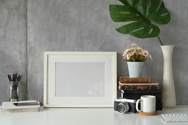 Poster di telaio vuoto mockup su area di lavoro hipster Foto Premium