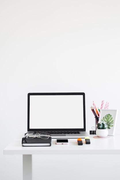 Posto di lavoro con laptop vicino occhiali, notebook, marcatori e telefono cellulare Foto Gratuite