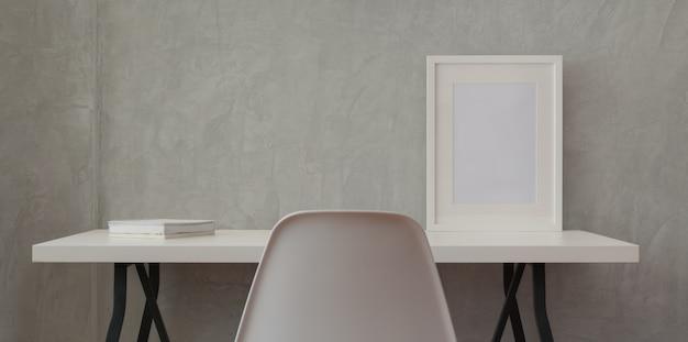 Posto di lavoro del sottotetto con lo scrittorio di legno bianco e la struttura del modello e libro bianco in parete grigia Foto Premium