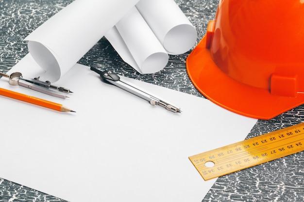 Posto di lavoro di ingegnere con schemi, bussola, matita e casco di sicurezza Foto Premium