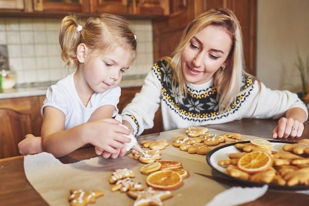 Posto di lavoro di pasticceria con le mani delle donne che decorano i biscotti di natale. panetteria a casa, dolce soleggiata, vacanze invernali. Foto Gratuite