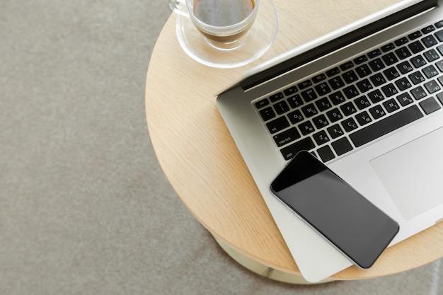 Posto di lavoro: laptop, telefono e un drink Foto Premium
