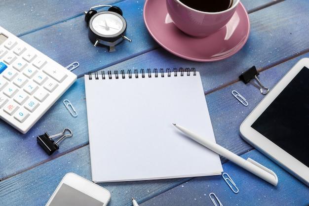 Posto di lavoro moderno con la tazza di caffè sulla tavola di legno Foto Premium