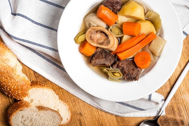 Pot-au-feu piatti caldi popolari della cucina tradizionale francese. manzo e verdure brasati con brodo di manzo in un piatto bianco su un tavolo di legno. pasto caldo invernale. Foto Premium