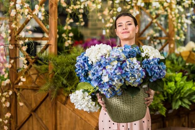 Pot della holding della giovane donna con i fiori in serra Foto Gratuite