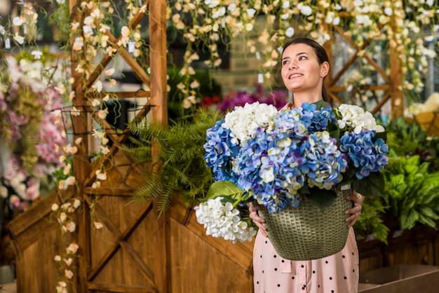 Pot grazioso della holding della donna con i fiori in serra Foto Gratuite
