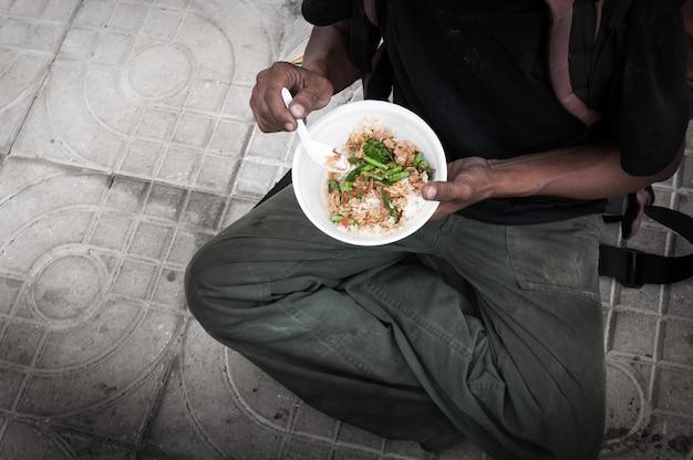 Povero senzatetto con le mani sporche che mangiano cibo al piano strada strada Foto Premium