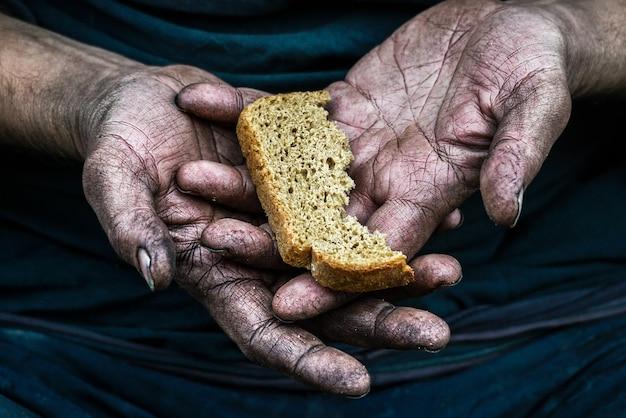 Povero senzatetto mani sporche con un pezzo di pane nella società moderna del capitalismo Foto Premium