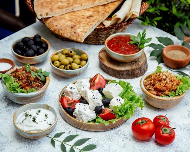 Pranzo all'aperto con insalate, olive e pane Foto Gratuite