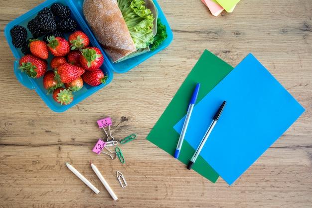 Pranzo in contenitore e quaderni sul tavolo Foto Gratuite