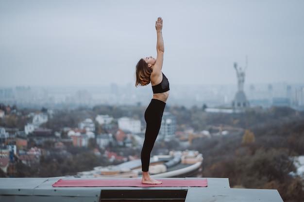 Praticare yoga donna sul tappetino sul tetto e fare esercizi di yoga Foto Gratuite
