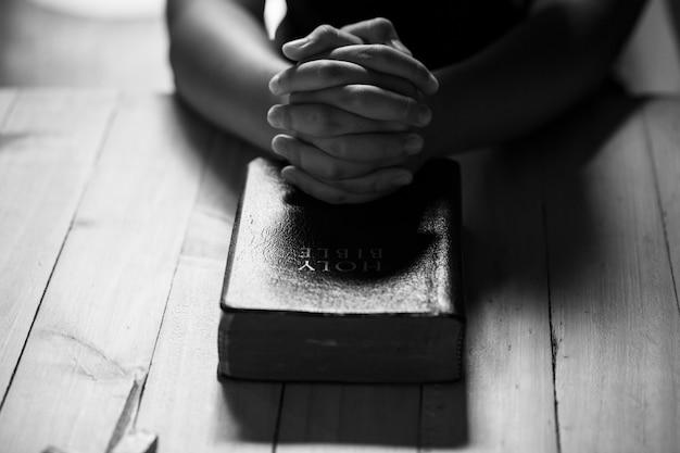 Pregare le mani degli adolescenti sulla vecchia bibbia Foto Gratuite