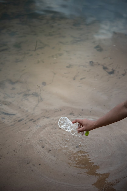 Prelevare a mano la bottiglia di plastica dall'acqua Foto Premium