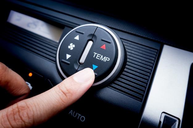 Premendo il dito sull'interruttore della temperatura di un sistema di condizionamento d'aria dell'automobile Foto Premium
