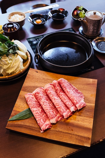 Premium rare slices wagyu a5 carne di manzo con trama marmorizzata su piastra quadrata in legno. Foto Premium