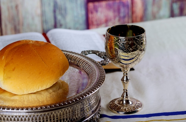 Prendendo la comunione. tazza di vetro con vino rosso, pane e sacra bibbia sul tavolo di legno Foto Premium