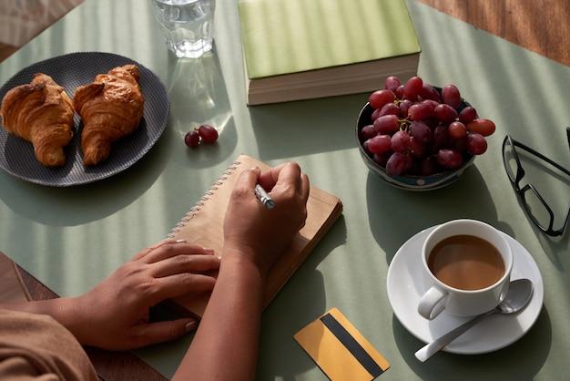 Prendere appunti al tavolo della cucina Foto Gratuite
