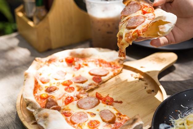 Prendi un pezzo di pizza., fetta di pizza italiana calda deliziosa fresca. Foto Premium
