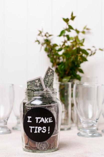 Prendo la punta di un bicchiere pieno di soldi e pianta in background Foto Gratuite