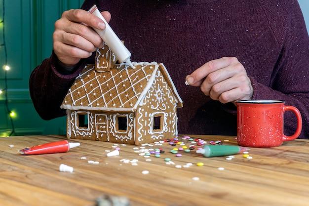 Preparare la casa di marzapane di natale. cottura e biscotti tradizionali di natale. Foto Premium