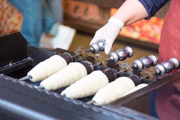 Preparare trdelnik. la tradizionale pasticceria dolce ceca venduta nelle strade di praga e in altre città della repubblica ceca. Foto Premium