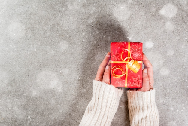 Prepararsi per le vacanze, natale. le mani femminili nella foto in un maglione caldo tengono un regalo in un involucro rosso con un nastro dorato. grigio, effetto neve, copyspace vista dall'alto Foto Premium