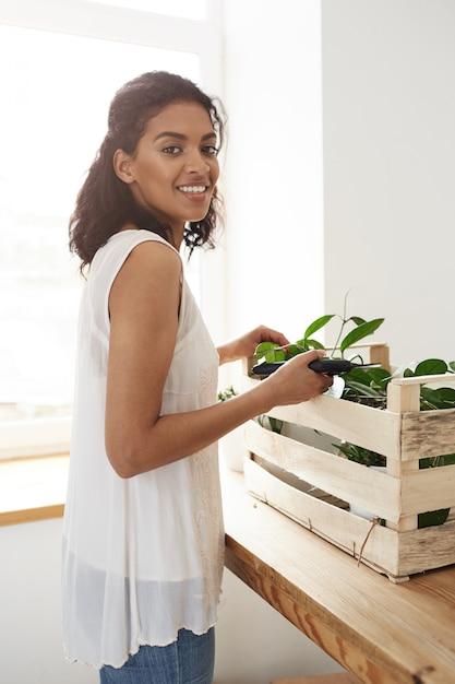 Preparazione allegra sorridente della donna per tagliare i gambi della pianta sopra la parete e la finestra bianche Foto Gratuite