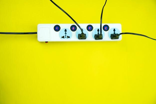 Presa e spina di energia elettrica su fondo di carta giallo Foto Premium