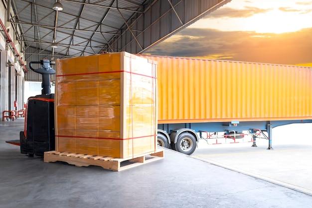 Presa pallet elettrico per carrello elevatore con carico di spedizione merce pallet con container camion Foto Premium