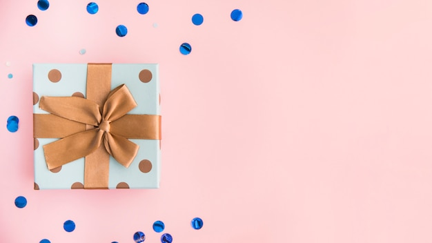Presente avvolto con fiocco marrone e nastro su sfondo rosa pastello Foto Gratuite