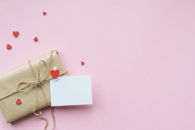 Presente avvolto in carta marrone artigianale e cravatta in corda di canapa. regalo romantico con cuori rossi decorativi. vista dall'alto. Foto Premium
