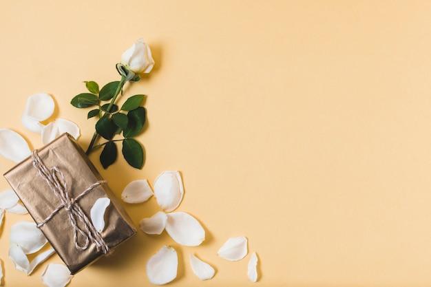 Presente con petali di rosa e copia spazio Foto Gratuite